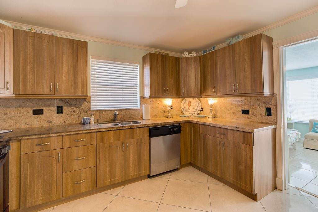 A beach house wedding means leisurely breakfasts and light meal preparation. This is the newly remodeled kitchen with Sun-Room on the right. It has convenient access to all areas; the dining and living area on one side, and the sun-room and pool on the other.