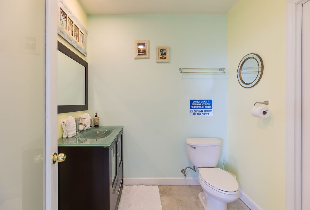 This bathroom adjacent to the Sun Room doubles as a pool bathroom. You will probably have guests staying at a local hotel but staying their days with you here. This beautiful bathroom is a gracious way for your guests to clean up after a day on the beach or in the pool. The walk-in shower is immense.